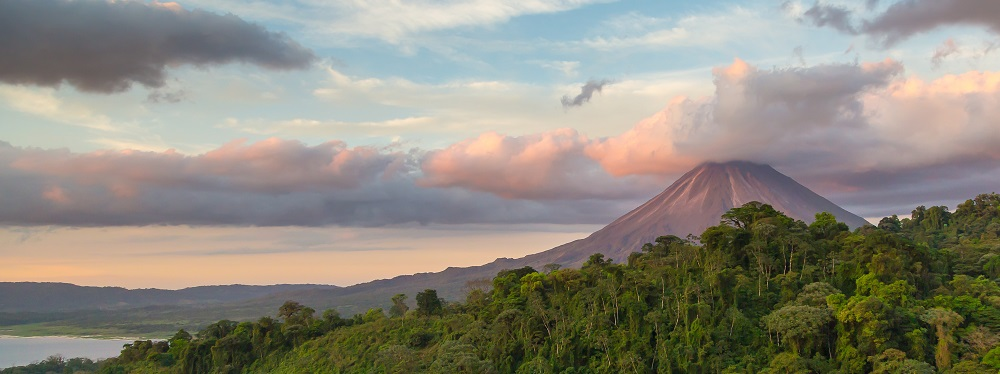 Arenal Volcano at Sunrise in Costa Rica, as the sun reflects on the newly formed clouds