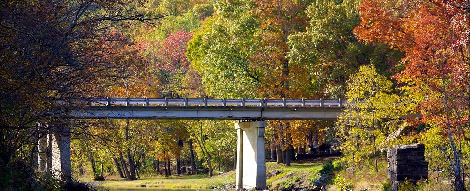 The Autumn colors surround the Lee Creek Bridge at Devil's Den State Park near Winslow, AR.