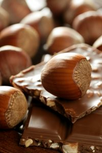 Hazelnuts and chocolate on brown wood enviroment at studio