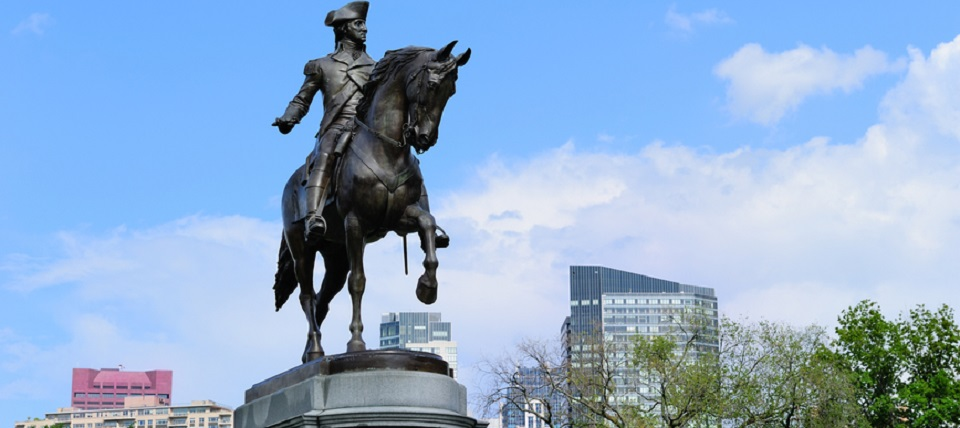George Washington statue as the famous landmark in Boston Common Park with city skyline and skyscrapers.