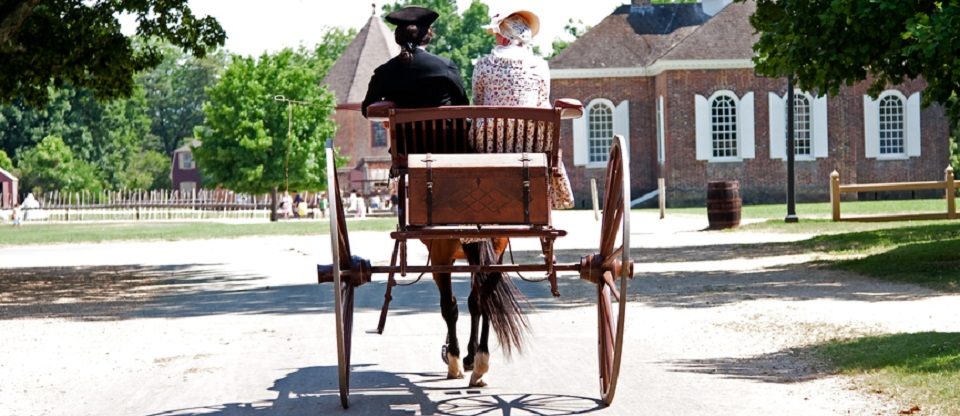 Rear view of a historical couple of a man and a woman dressed in Colonial American style on a brown carriage with treasure chest pulled by a horse in Colonial Williamsburg, Virginia