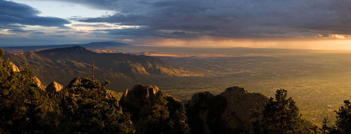 Panorama of majestic sunset over the Chihuahuan Desert and the city of Albuquerque, New Mexico, as seen from the peak of the Sandia Mountains