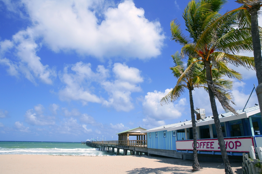 Fort Lauderdale beach cafe with tropical palm trees and blue sky